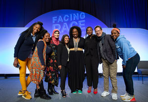 Eight people standing together on stage including Jeff Chang; Tarana Burke; Rinku Sen; and Alicia Garza