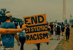 """This is a photo of protestors, which includes one person holding up a sign that says. """"End Systemic Racism."""""""