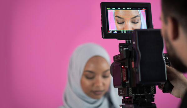 A person in hijab in front of a video camera.
